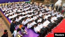 資料照:中國南京一群學生在一個家具展上在一個墊子上躺下。
