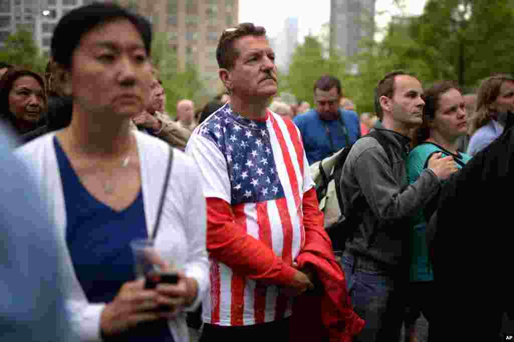 جمعیتی افسرده و محزون به تصویر پرزیدنت اوباما بر صفحه تلویزیون هنگام ایراد سخنرانی در جریان مراسم وقف موزه ملی یادبود ۱۱ سپتامبر نگاه می کند.