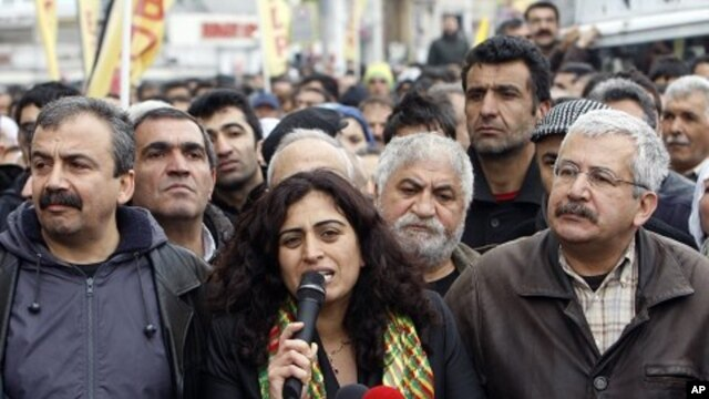Peace and Democracy Party (BDP) Parliamentarians Sebahat Tuncel (C) and Ufuk Uras (R) attend a protest against the High Election Board's decision in central Istanbul, April 19, 2011
