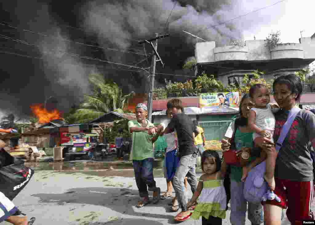 Residents evacuate as houses burn in a residential district after a clash between government soldiers and Muslim rebels in Zamboanga, Philippines, Sept. 12, 2013.