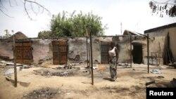 Une femme débour devant des maisons incendiées lors d'une attaque de Boko Haram au village de Michika, dans l'Etat d' Adamawa dimanache 10 mai 2015.