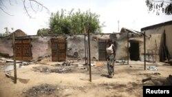 Seorang perempuan berdiri di depan rumahnya di kota Michika di negara bagian Adamawa, Nigeria yang hangus terbakar (10/5).