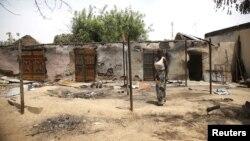 Une femme devant des maisons incendiées après une explosion provoquée par des combattants de Boko Haram dans l'Etat d'Adamawa , le 10 mai 2015, au Nigeria.