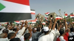 People wave Sudanese flags at soldiers during a celebration march outside Sudan's Defence Ministry in Khartoum, Sudan, April 20, 2012.