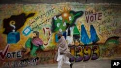 Warga berjalan melewati grafiti yang mendorong masyarakat untuk memberikan suaranya di provinsi Kandahar, Afghanistan (12/3). (AP/Anja Niedringhaus)