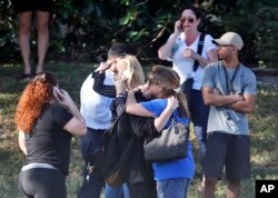 Anxious family members wait for news of students as two people embrace, Feb. 14, 2018, in Parkland, Fla.
