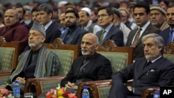 FILE - Afghan President Ashraf Ghani, center, former President Hamid Karzai, left, and Afghan chief executive Abdullah Abdullah, right, attend during a ceremony marking the first anniversary of the death of Former Afghan Vice President Marshal Mohammed Qa