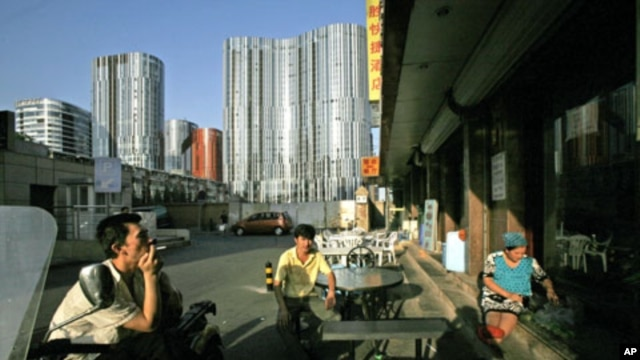 Uighurs rest outside a Xinjiang restaurant in front of commercial buildings in Beijing, (File)