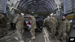 英军人员在停在法国一陆军基地的一架英国C17运输机内装载的法军医疗装甲车前走过。英美都在向法国在马里的行动提供支持。(2013年1月14日)