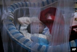 FILE - A newborn lies in her crib at the state-run al-Zuhour orphanage, in Mosul, Iraq, Aug. 19, 2018. Here, it's a mix of infants born to Iraqi women who were enslaved by militants and older children whose parents are jailed; some were simply abandoned in the chaos that follows a war.