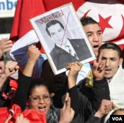 Warga di Tunis melakukan unjuk rasa sambil membawa poster Presiden Ben Ali yang melarikan diri ke Arab Saudi.