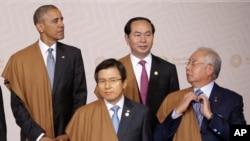 PM Malaysia Najib Razak membetulkan dasinya sambil menunggu Presiden AS Barack Obama, kiri atas, PM Korsel Hwang Kyo-ahn, kiri depan, dan Presiden Vietnam Tran Dai Quang untuk foto bersama pada pertemuan puncak tahunan APEC (20/11). Lima, Peru. (foto: AP Photo/Martin Mejia)