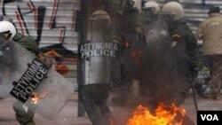 Para demonstran Yunani yang marah atas langkah-langkah penghematan pemerintah melempar bom molotov ke arah polisi di Athena (10/2).