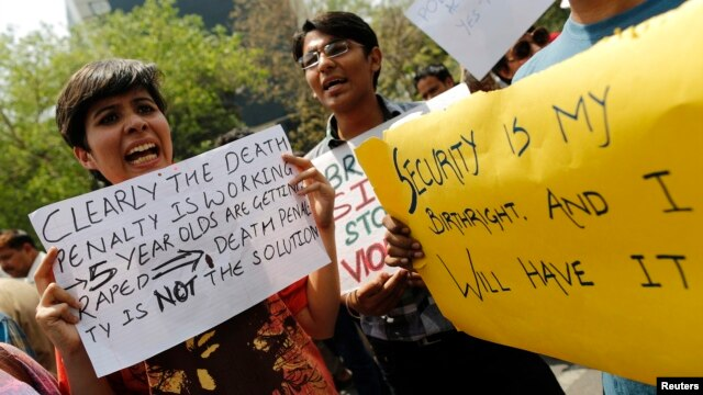 Demonstrators hold placards as they shout slogans during a protest outside police headquarters in New Delhi, April 20, 2013, after a five year-old girl was allegedly raped and tortured.