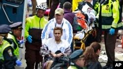 15일 미국 보스턴 마라톤 대회장에서 연쇄 폭탄 테러가 발생한 가운데, 경찰과 구조대가 부상자를 옮기고 있다.