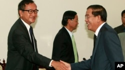Cambodian Prime Minister Hun Sen, right, shakes hands with opposition leader Sam Rainsy before a meeting at the National Assembly in Phnom Penh, Cambodia, Sept. 17, 2013.