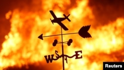 FILE - A weather vane is pictured on a ranch during the Creek Fire in the San Fernando Valley north of Los Angeles, in Sylmar, California, Dec. 5, 2017.