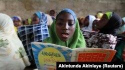 Une jeune fille lit des versets dans une école coranique le 2e jour du mois sacré du Ramadan dans la ville de Kano, au nord du Nigeria, le 21 juillet 2012.