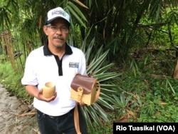 "Sekjen Perpubi Dudi Darma Bakti menunjukkan gelas bambu dan tas bambu yang dipamerkan dalam ajang ""Bambu is Wonderful"" di Bandung, Senin (26/11/2018) sore. Dia mengatakan bambu bisa jadi 1500 produk turunan. (Foto: Rio Tuasikal/VOA)"