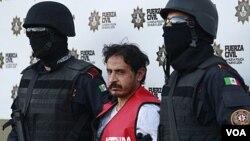 Polisi di Monterrey, Meksiko menunjukkan tersangka pembakar kasino, Baltazar Saucedo Estrada (tengah) kepada media (6/1).