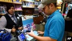 Hugo Roque, de Glendale, California, hace una compra en una tienda Disney.