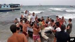 Italian Coast Guard officers, holiday-goers help migrants off boat near Siracusa, Aug. 15, 2013 file photo.