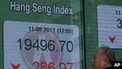 A man walks past a panel displaying the Hang Seng Index during a midday break, outside a bank in Hong Kong, August 11, 2011