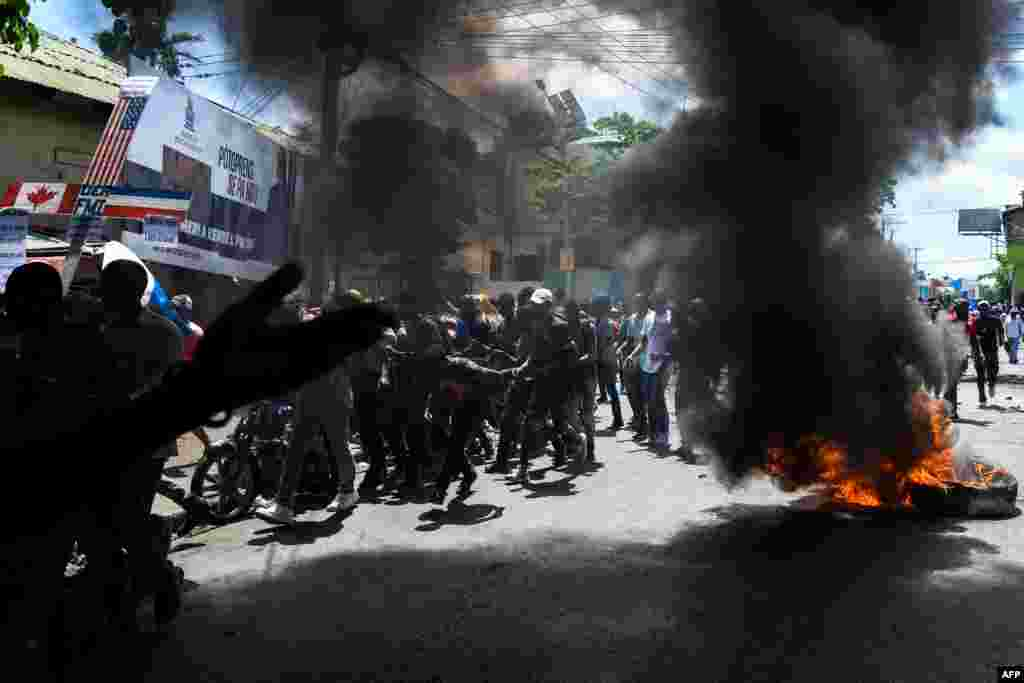 Demonstrators walk past burning tires during a protest march against the ruling government in Port-au-Prince, Haiti, on June 13, 2019.