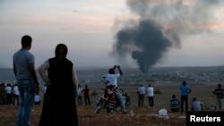 Người Kurd ở Thổ Nhĩ Kỳ theo dõi chiến sự tại Kobani gần biên giới Syria-Thổ Nhĩ Kỳ. Chính phủ Thổ Nhĩ Kỳ không cho các lực lượng tăng viện của người Kurd được tới Kobani.