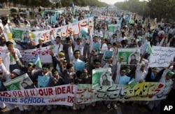 FILE - Students chant slogans while holding banners and posters showing Mumtaz Qadri, the killer of Punjab Governor Salman Taseer, during a rally to protest against any attempts to modify blasphemy laws, in Karachi, Pakistan, Jan. 20, 2011. Qadri was eventually executed in prison.