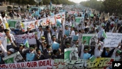 FILE - Students chant slogans while holding banners and posters showing Mumtaz Qadri, the alleged killer of Punjab governor Salman Taseer, during a rally to protest against any attempts to modify blasphemy laws, in Karachi, Pakistan, Jan. 20, 2011. Pakistani authorities on Feb. 29, 2016, hanged Qadri, a former police bodyguard.