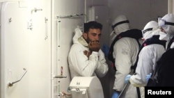 2015年4月20日一幸存移民(左)乘意大利海岸警卫队船只到意大利达卡塔尼亚