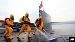 中國海軍發布的照片顯示,在青島潛艇基地,穿著防護服的水兵清潔核潛艇
