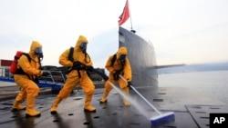 Thủy thủ Trung Quốc rửa và khử trùng tàu ngầm hạt nhân trong một cuộc diễn tập tại căn cứ tàu ngầm Thanh Đảo ở tỉnh Sơn Đông phía đông Trung Quốc, ngày 27/10/2013