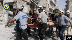 FILE - In this photo, provided by the Syrian Civil Defense White Helmets, rescue workers work the site of airstrikes in the al-Sakhour neighborhood of the rebel-held part of eastern Aleppo, Syria, Sept. 21, 2016. Violence in Aleppo has surged in recent days as a U.S.-Russia-brokered cease-fire collapsed after one week.