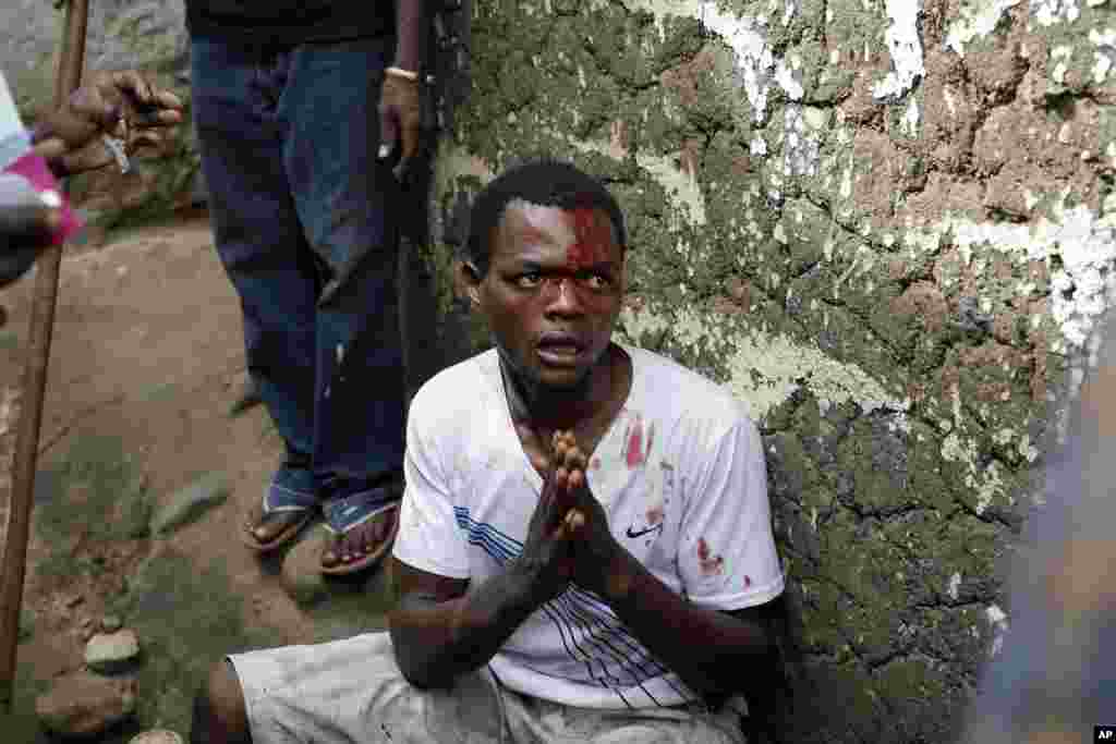Jean Claude Niyonzima pleads for his life as he is surrounded at his house by demonstrators in Bujumbura, May 7, 2015.