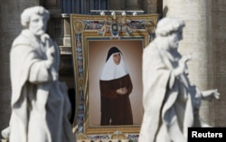 A tapestry showing Maria Isabel Salvat Romero hangs from a balcony as Pope Francis leads the mass for a canonization in Saint Peter's Square at the Vatican, Oct. 18, 2015.