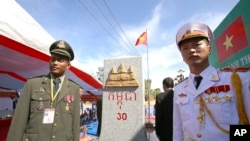 FILE PHOTO - A Cambodian army officer, left, and a Vietnamese army officer stand in front of a newly launched border mark (on the Cambodian side) in between Gia Lai province of Vietnam and Rattanakiri of Cambodia on Saturday, Dec. 26, 2015.