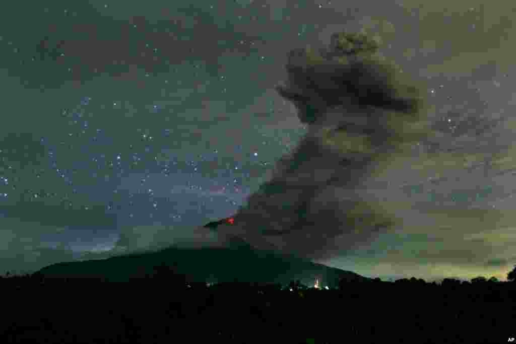 Mount Sinabung spews volcanic ash into the air as seen from Tiga Pancur, North Sumatra, Indonesia, Nov. 24, 2013.