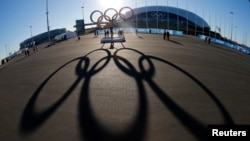 File - The Olympic rings are cast in shadow as the sun sets behind the Bolshoy Ice Palace as preparations continue at the Olympic Park for the 2014 Winter Olympics in Sochi, Russia, Feb. 3, 2014.