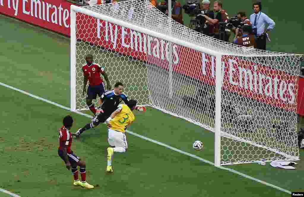 Brazil's Thiago Silva scores his team's first goal past Colombia's goalkeeper David Ospina at the Castelao arena in Fortaleza, July 4, 2014.