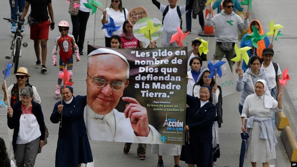 """Para biarawati membawa poster Paus Fransiskus dan pesan dalam bahasa Spanyol: """"Saya meminta Anda dalam nama Tuhan untuk Membela Bumi"""" dalam pawai untuk memerangi perubahan iklim Bogota, Colombia, 29 November 2015."""