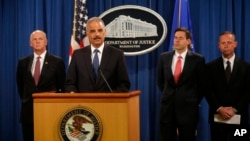 FILE: U.S. officials announced charges against five Chinese military officers at a Washington, D.C., news conference May 19, 2014. Attorney General Eric Holder, second from left, is joined by, from left, David Hickton, John Carlin and Robert Anderson.
