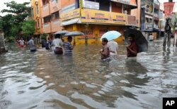 People wade through a flooded street in Chennai, in the southern Indian state of Tamil Nadu, Dec. 2, 2015.
