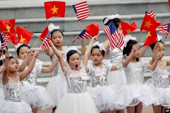每当越南主席府举行的迎美国总统川普的典礼前,小挥舞两国国旗(2017年11月11 天)