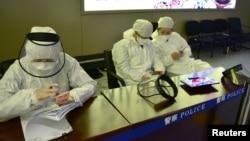 中国黑龙江省哈尔滨机场的公安人员身穿防护服进行旅客登记。(2020年4月11日)
