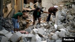 4일 이스라엘 군이 가자지구 북부 난민시설을 공습한 후, 팔레스타인인들이 무너진 건물 잔해를 수색하고 있다.