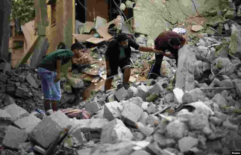 Palestinians search for the remains of bodies under the rubble of the Abu Nejim family house which witnesses said was destroyed by an Israeli air strike in Jabaliya refugee camp in the northern Gaza Strip, August 4, 2014.