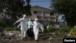 A burial team wearing protective clothing remove the body of a person believed to have died of Ebola in Freetown, Liberia, Sept. 28, 2014.