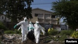 A burial team wearing protective clothing, remove a body of a person suspected of having died of the Ebola virus, in Freetown September 28, 2014.